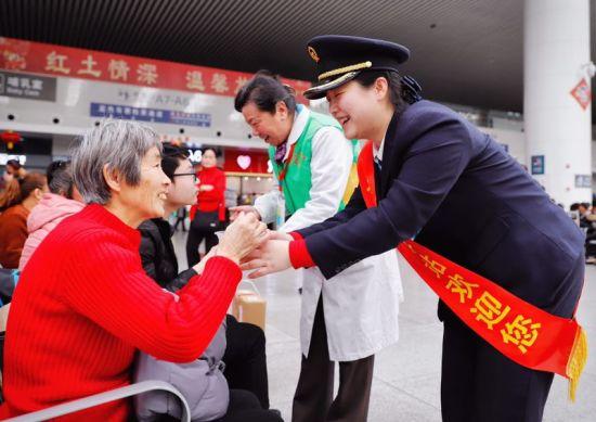 图为南昌站客运工作人员和南铁志愿者正在给候车室的旅客送汤圆.